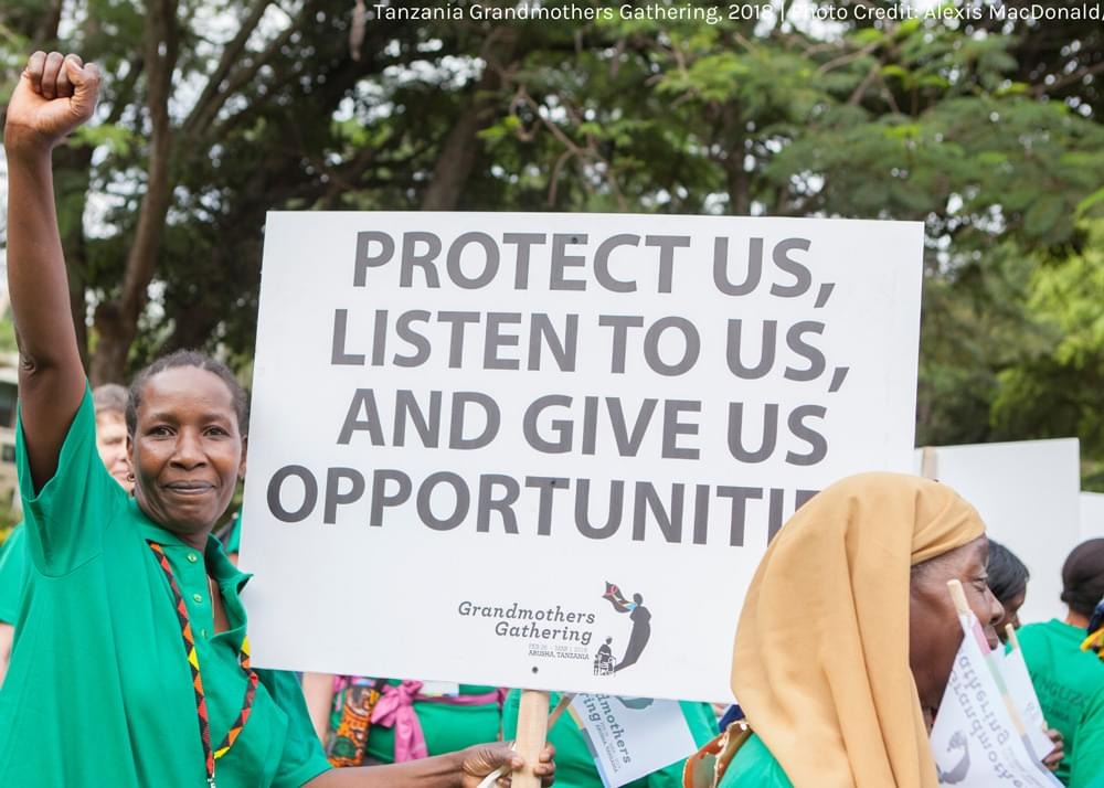 wman with sign reading: protect us listen to us and give us opportunities