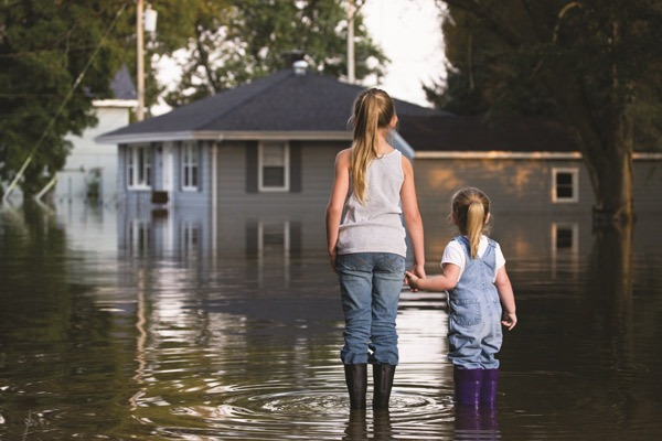 Children standing by flooded home