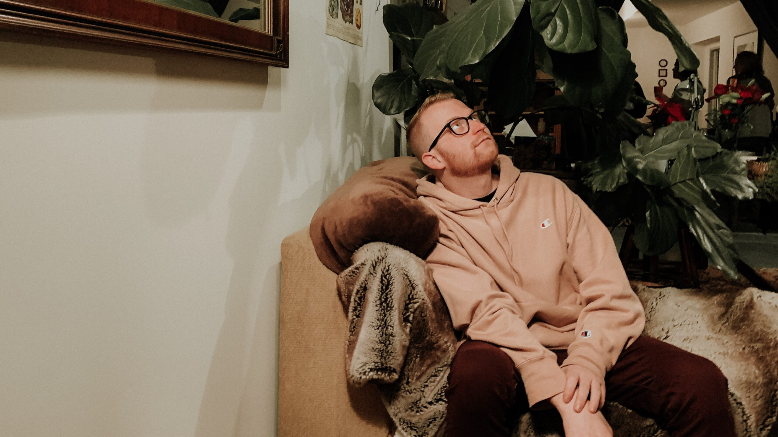 A photo of Eric Michael underneath a fiddle leaf fig, indoor plant