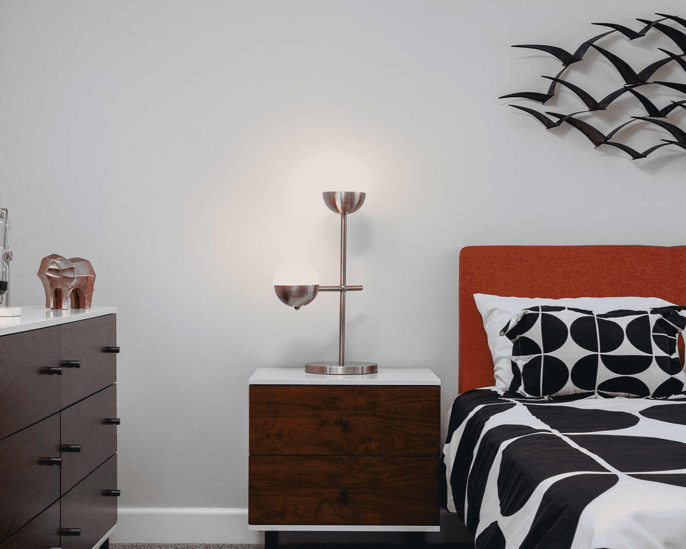 Bedside table with lamp in between cabinet with gold elephant sculpture on top and a bed with orange head board, black and white bedding, and a bird art sculpture above