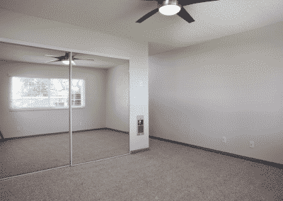 Empty bedroom with ceiling fan, storage, and closet