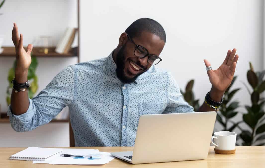 A man looking at his laptop smiling