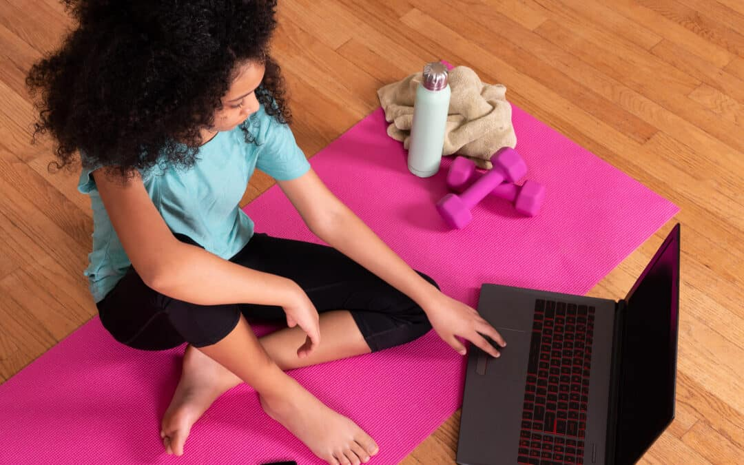woman sitting on an exercise mat with on hand on the laptop