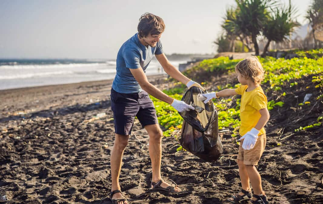 a man and a child on the beach putting waste in a trash bag