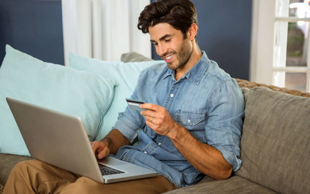 a man sitting on a couch with his laptop and holding a credit card