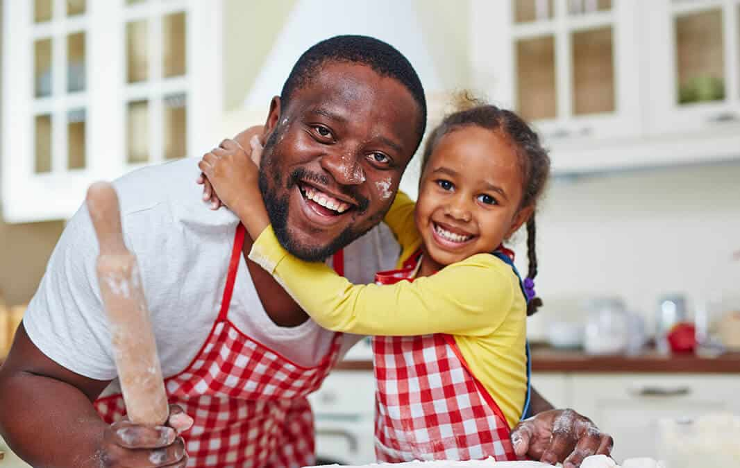 man and child smiling in kitchen