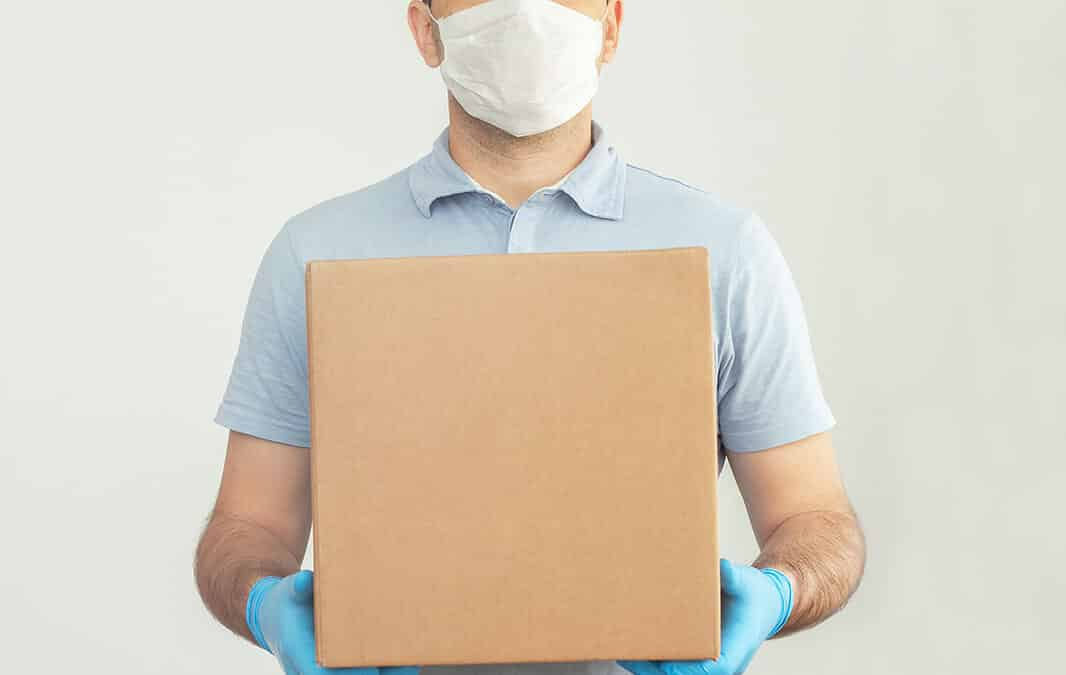 Person in mask holding box