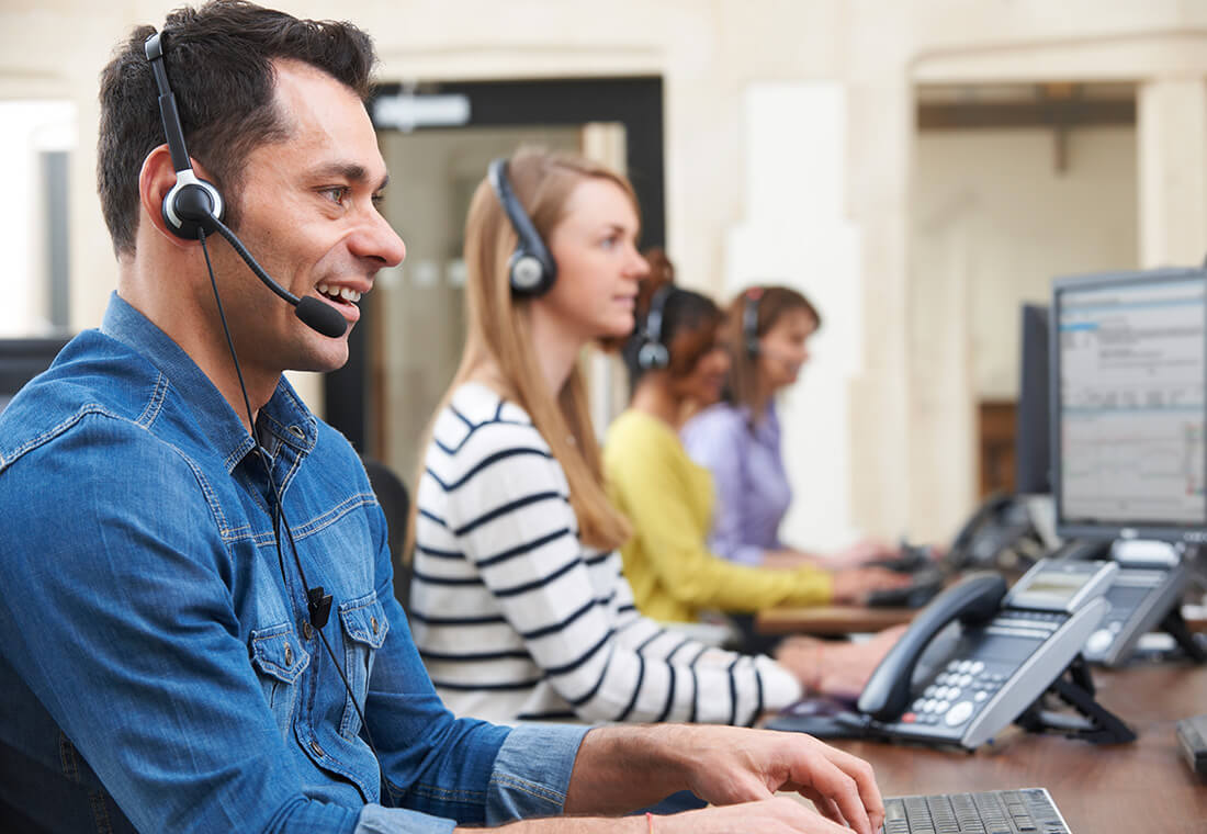 Customer service agent, with 3 others in the background, smiling while speaking to a customer on his headset.