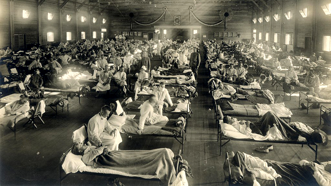 Emergency hospital during influenza epidemic, Camp Funston, Kansas. Emergency hospital during influenza epidemic (NCP 1603), National Museum of Health and Medicine. Description: Beds with patients in an emergency hospital in Camp Funston, Kansas, in the midst of the influenza epidemic. The flu struck while America was at war, and was transported across the Atlantic on troop ships. Date: circa 1918 Photo ID: NCP 1603 Source Collection: OHA 250: New Contributed Photographs Collection, Otis Historical Archives, National Museum of Health and Medicine. PD-US-expired.