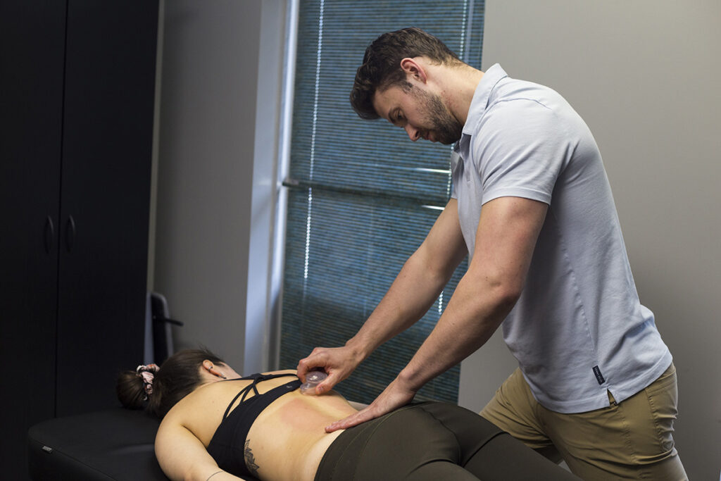 Man doing cupping on a woman.