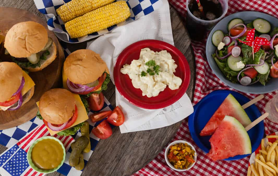 Top view of burgers, mashed potato, corn on the cob, salad and watermelon slices
