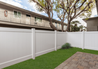 grassy backyard with fence and pavement