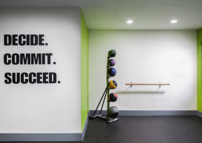 White wall with Decide, Commit, Succeed signs with ballet bar and medicine balls