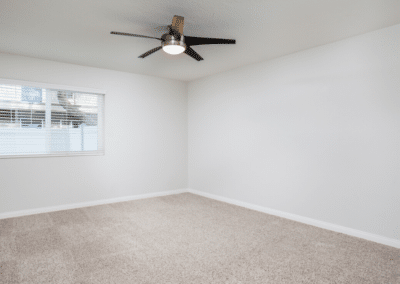Carpeted bedroom with Ceiling fan and Window