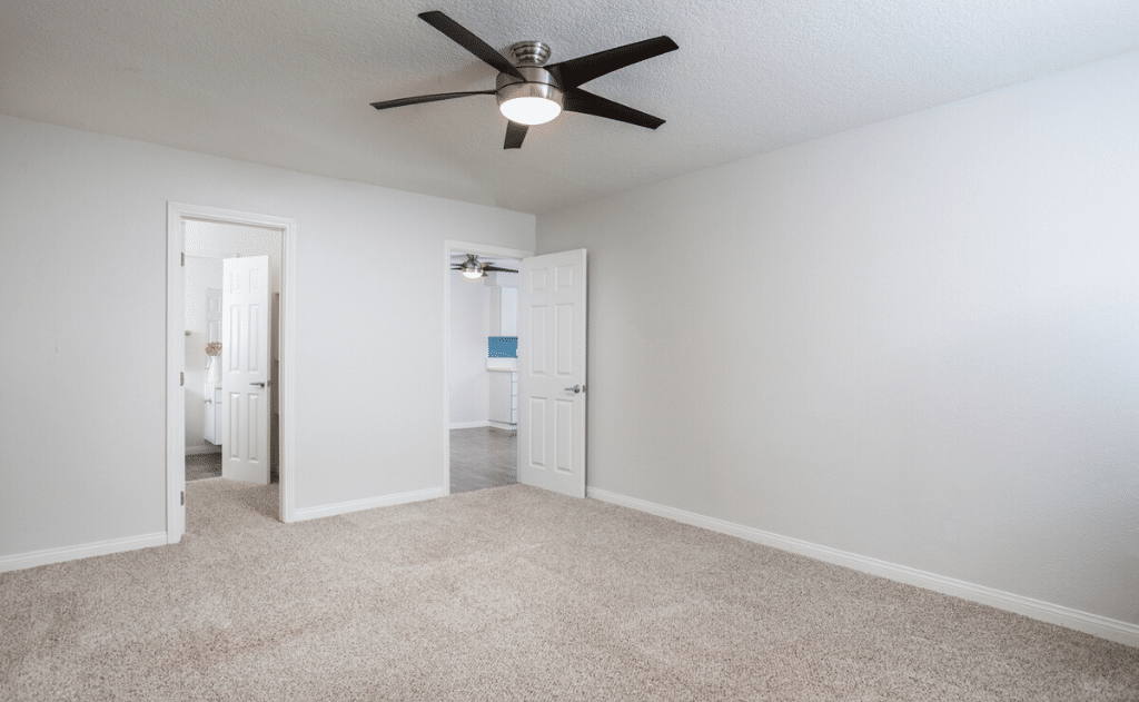 5800 Apartment home interior apartment unit with white walls, carpet, and ceiling fan