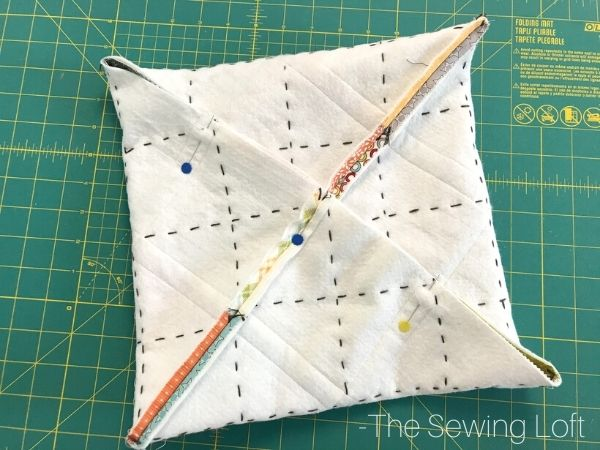 Learn how easy it is to create an on point patchwork pillow with the help of origami.