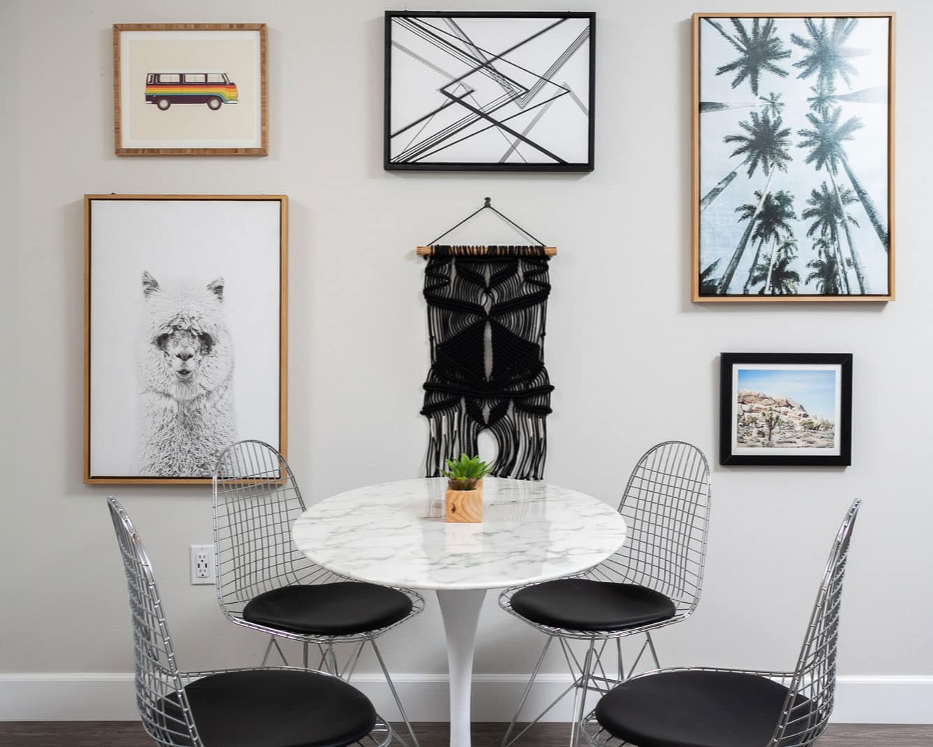 Dining area with marble round table, four metal chairs, and paintings on the wall