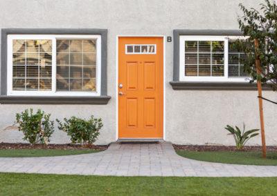 Closed orange door with natural green plants