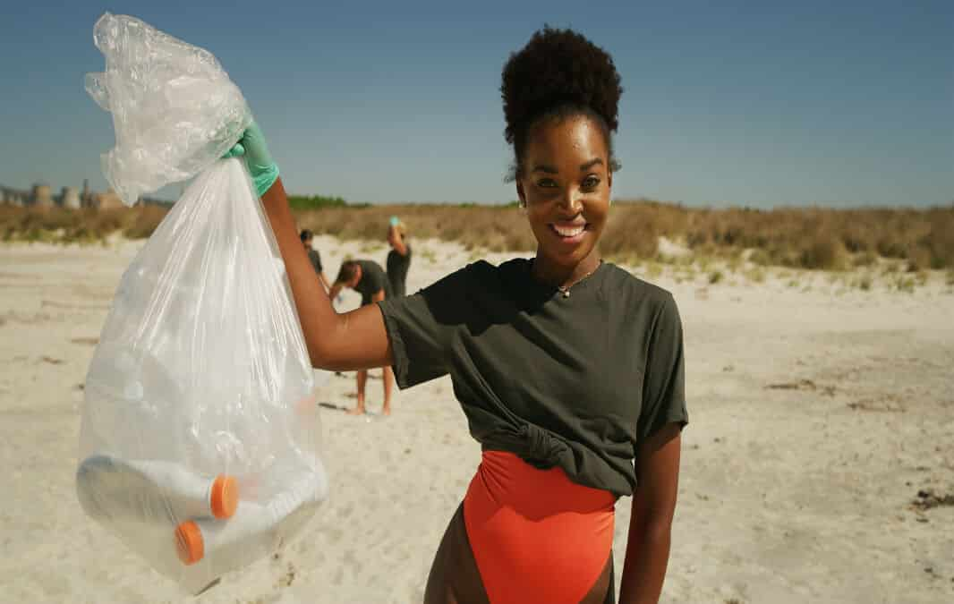 a woman on the beach smiling holding up a full trash bag