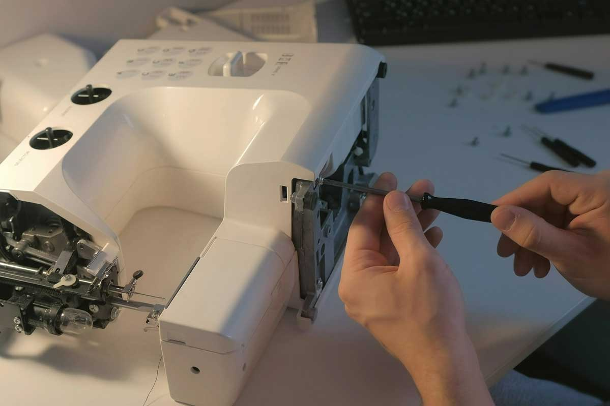 Repairman-master-is-collecting-and-testing-sewing-machine-after-repairing-sitting-at-table-in-workshop