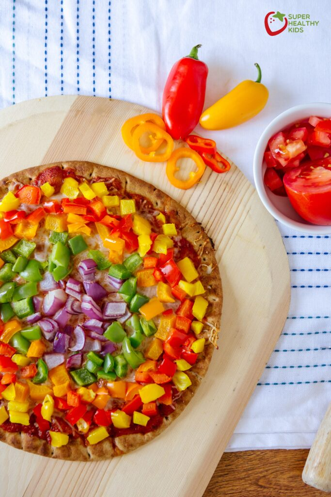 Image of bell pepper pizza kept on a wooden tray along with a bowl of chopped tomatoes