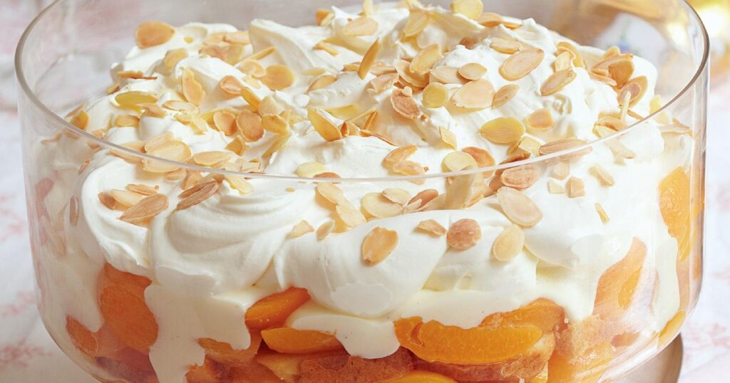 Image of creamy and delicious apricot sponge cake trifle in a transparent bowl