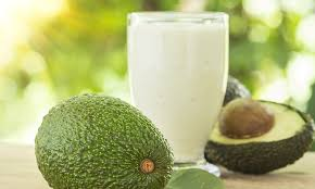 Image of a cup of Avocado Lassi in a tumbler along with a whole and cut avocado fruit displayed