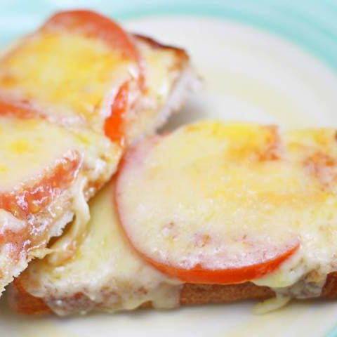 Image of a cheesy tomato toast kept on a porcelain plate