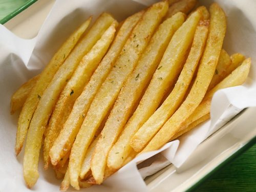 Image of crispy french fries kept on a tissue paper in a serving dish