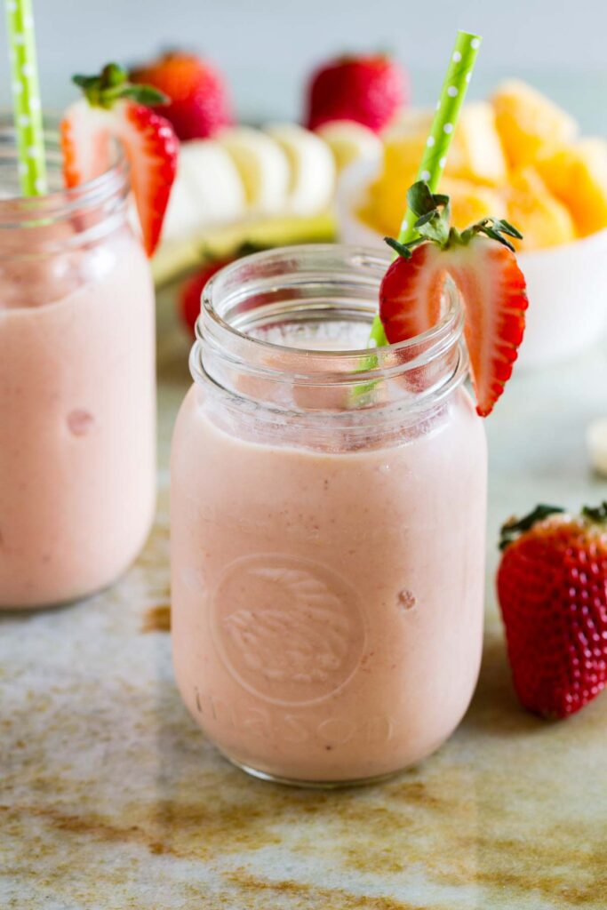 Top 10 Snacks Under 10 mins - Image of strawberry and banana smoothie served in a glass jar along with fruits kept in a plate.