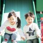 すべり台で遊ぶ笑顔の子供
