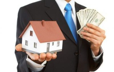 a man in a suit holding a toy house in one hand and fanning out a bundle of cash in his other hand
