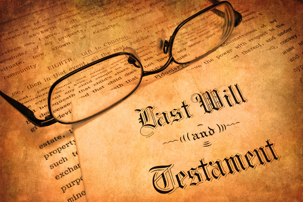 a picture of eyeglasses resting on a yellowed copy of a will and testament