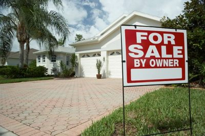for sale by owner sign in the ground in the front yard of a house
