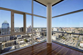 looking out a condos window from high up. Has a hardwood flooring
