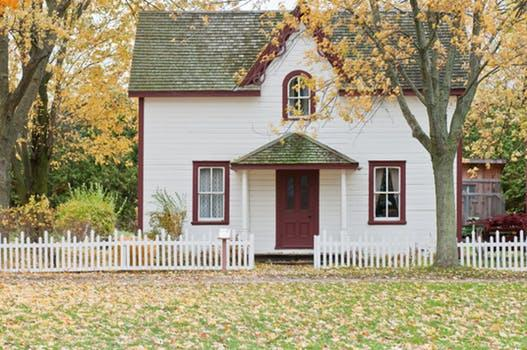 house sitting in winter and fall with leaves fallen and yellow on the grass in front of the home