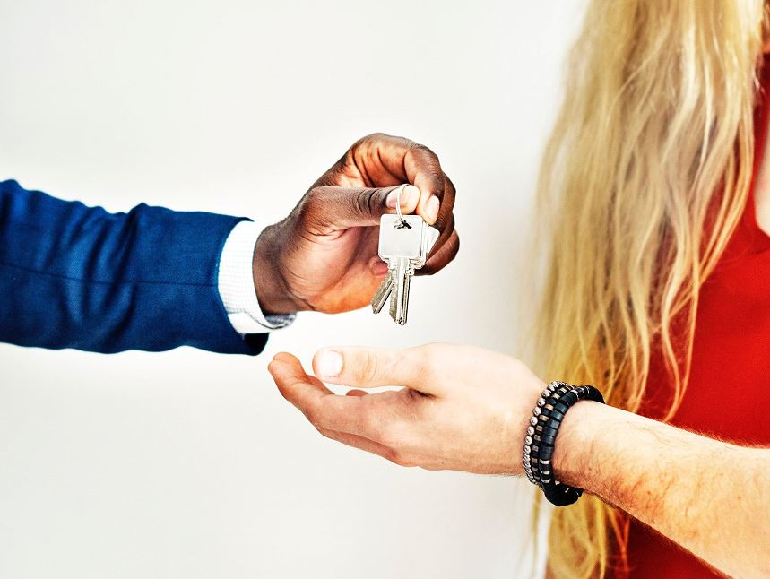 woman hanging over a keys to a man placing in his hand