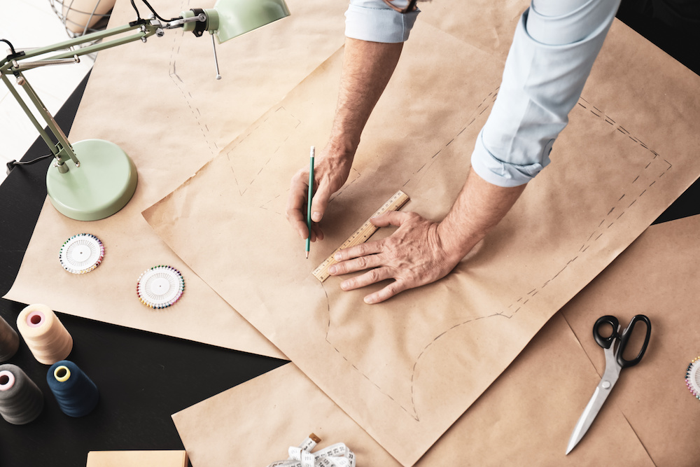 Mature tailor working with sewing pattern in atelier