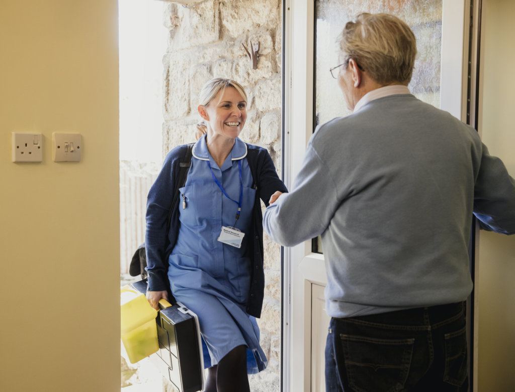 Nurse at the Door Making a House Call to a Senior Man