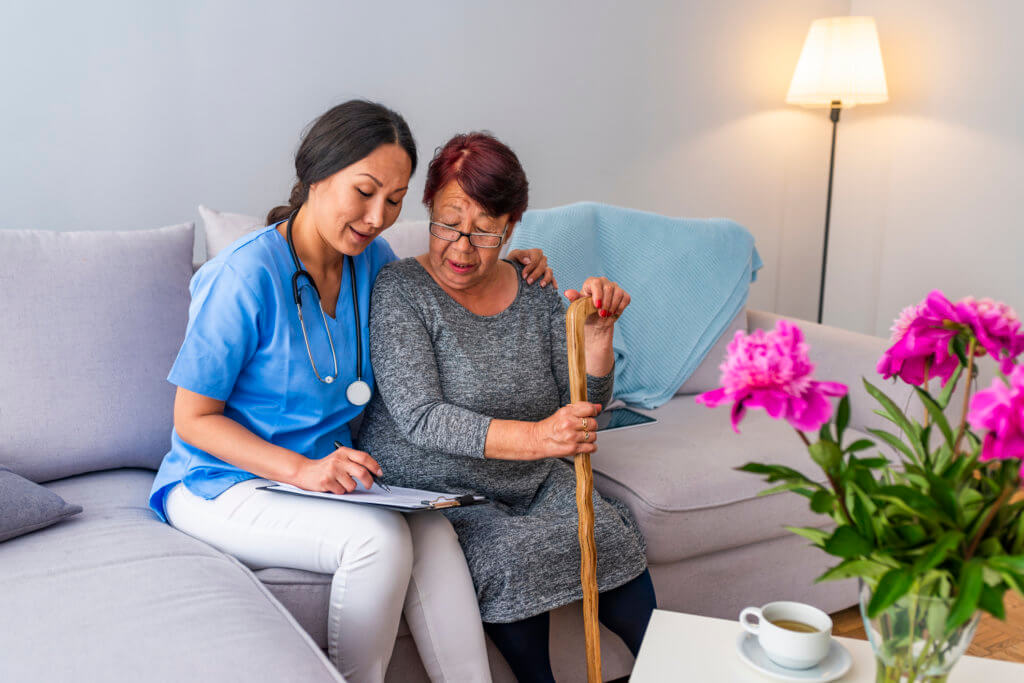 Smiling senior woman with walking stick and helpful caregiver holding her hand.