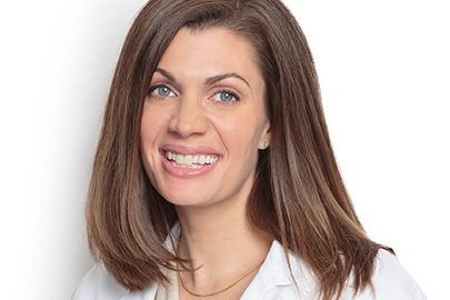 Anne Peled, MD smiling with short brown hair and lab coat on