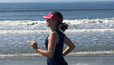 Anne Peled, MD running on the beach with her hair up and red cap on