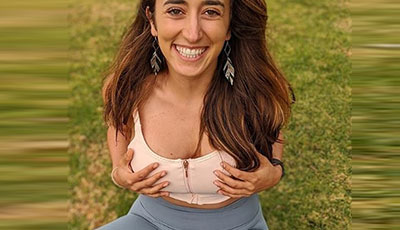 Sarafina Nance sitting on the grass smiling holding her breasts as she is wearing a compression sports bra