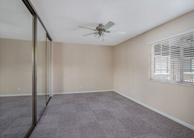 Empty bedroom with mirrored closet and ceiling fan