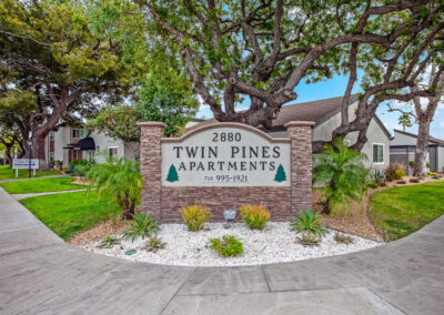 Twin Pines apartment sign with pathway and landscaping