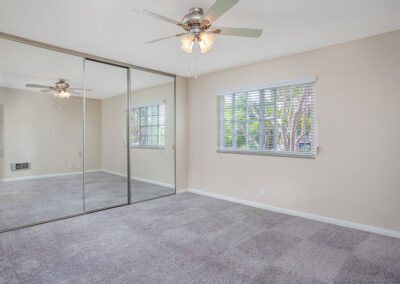 Empty bedroom with ceiling fan and mirrored closets