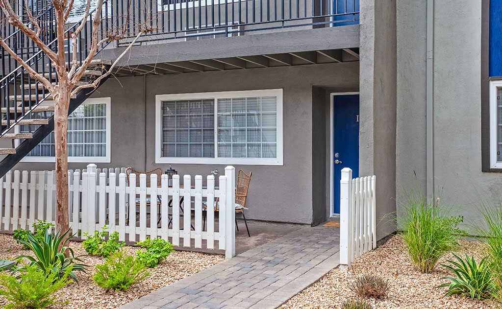 Twin pines apartment homes unit with white fence and blue doordoor