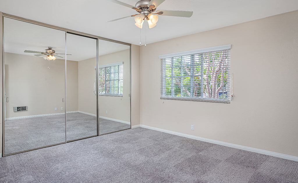 Empty bedroom with ceiling fan and mirrored closet