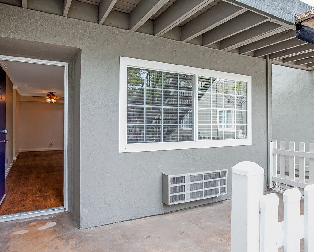 Open Door to the Apartment with view of porch and white picket fence