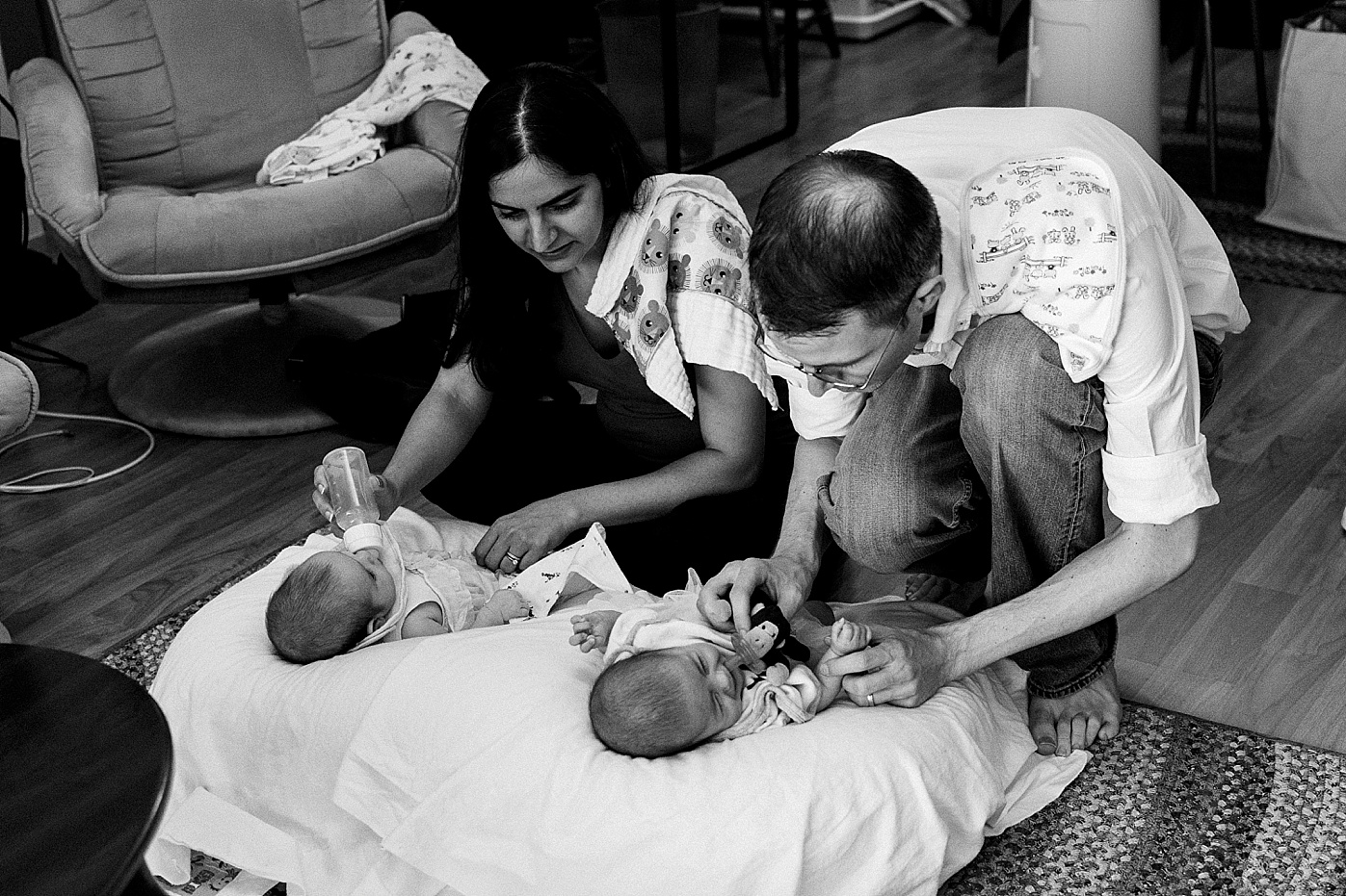 mom and dad feeding twin newborn baby girls documentary candid family photography